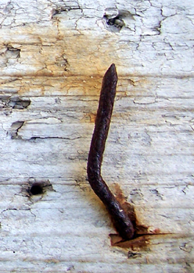 rusty nail on driftwood